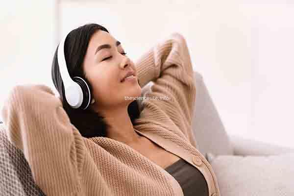 Asian woman listening to music wearing headphones