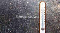 Wooden weather Thermometer on black background. Top view.