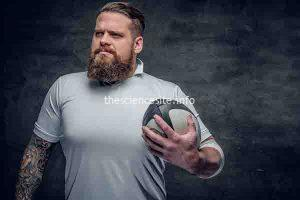 Portrait of bearded rugby player with tattoos on his arms holds a game ball.